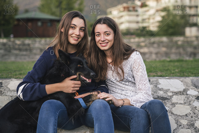 Sisters with dog in park