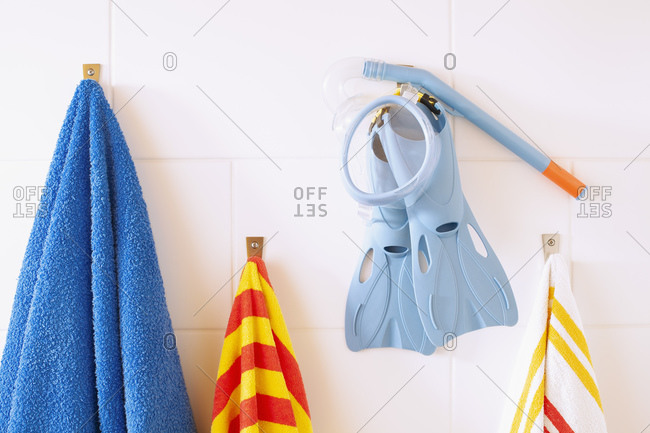 Towels, snorkel tube and flippers hanging on bathroom wall