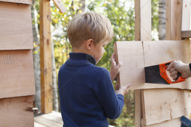 Boy learning to build treehouse with adult