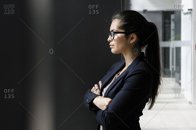 Young businesswoman taking break at corridor of office building