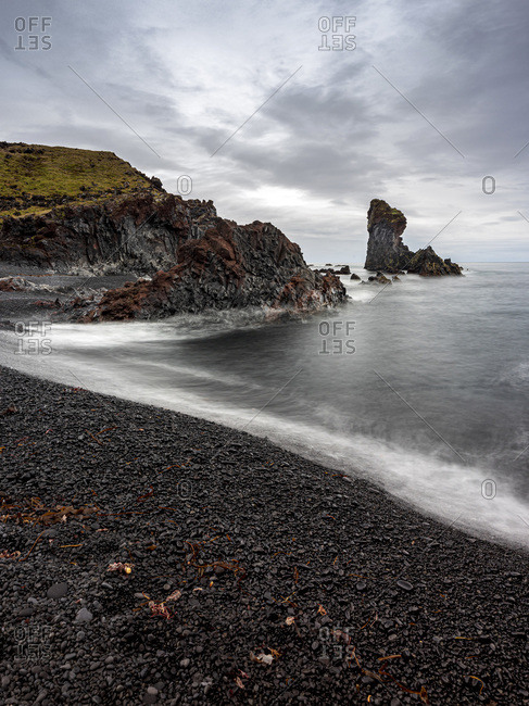 Volcanic rock formations on black sand beach, Snaefellsbaer, Vesturland, Iceland