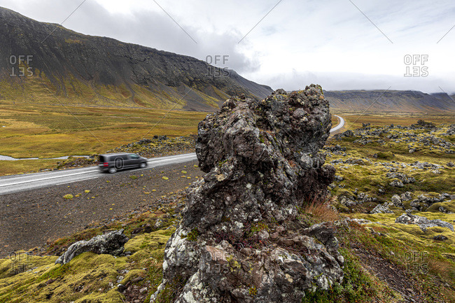 Vehicle driving on road along volcanic lava field, Snaefellsbaer, Vesturland, Iceland