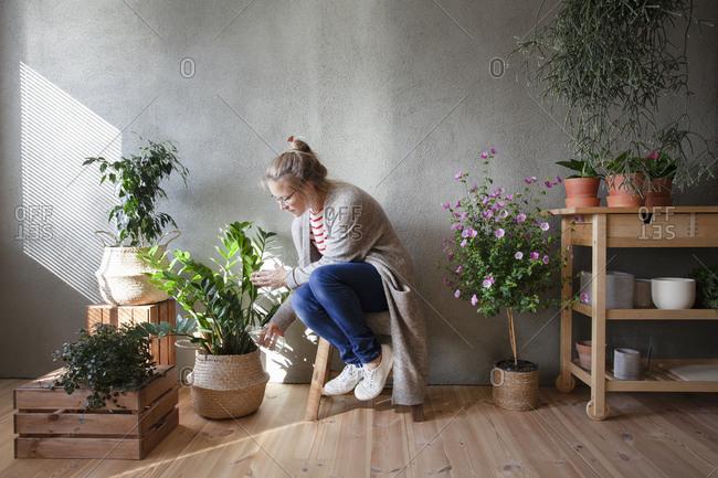 Woman tending to potted plants in indoor garden