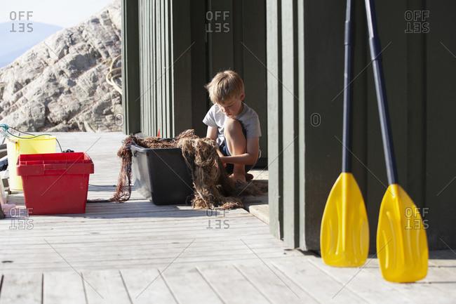 Boy disentangling fishing net inside pail on pier