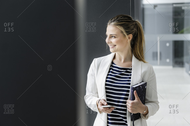 Female student with notebook at corridor of office building