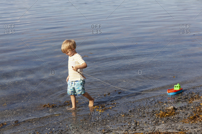 Boy playing with toy boat on beach