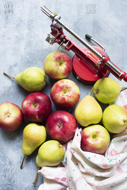 Apple peeler with apples and pears on table