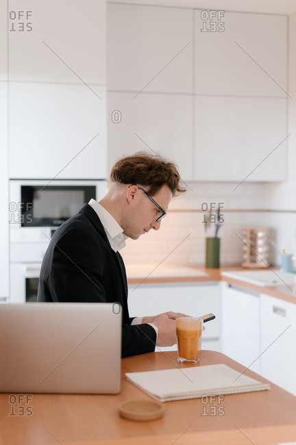 A man working from home checks his phone