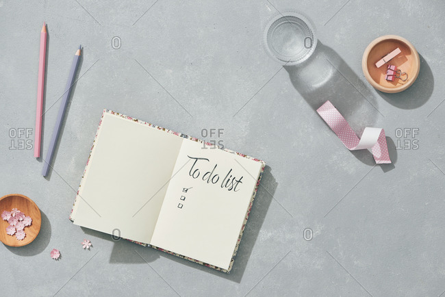 Creative flat lay mockup design of workspace desk with blank notebook, glass of water, stationery with copy space background