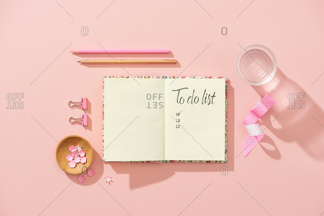 Feminine workspace with notebook, cup of water, pink flower, pencil.