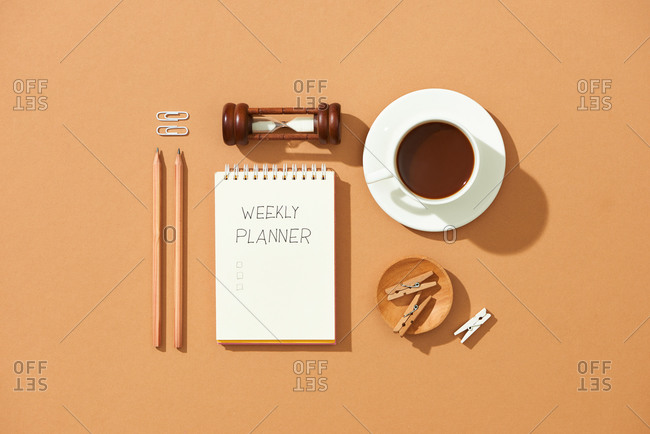 Notebook, pencil,  stationery and hourglass on table