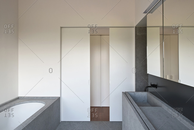 Interior of a modern bathroom with concrete elements and partially opened doors