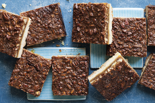 Squares of pecan nut bars arranged on a blue background