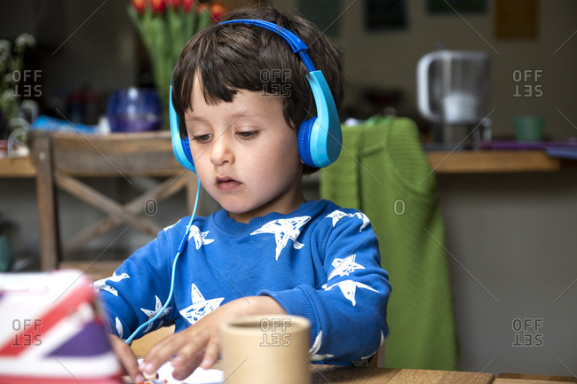 Young boy doing distance learning on a tablet with headphone