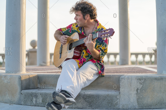 Talented male musician in colorful shirt playing acoustic guitar and singing songs while performing on city street and looking away