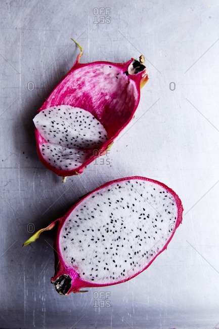 Dragon fruit cut open on marble plate on a light background,