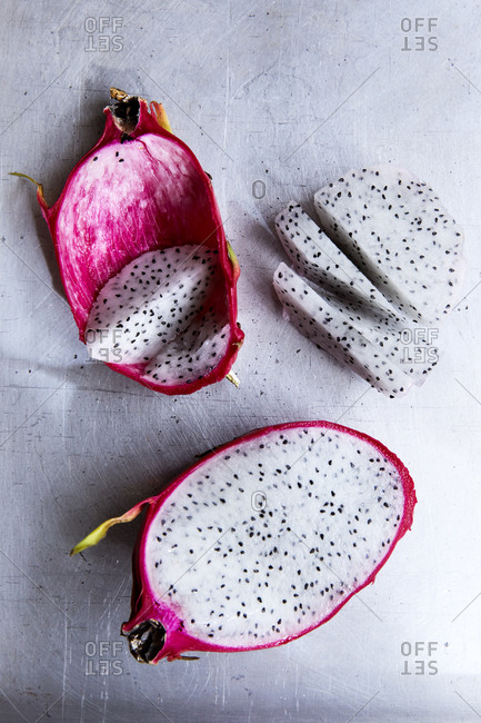 Side view of dragon fruit cut open on a light background,