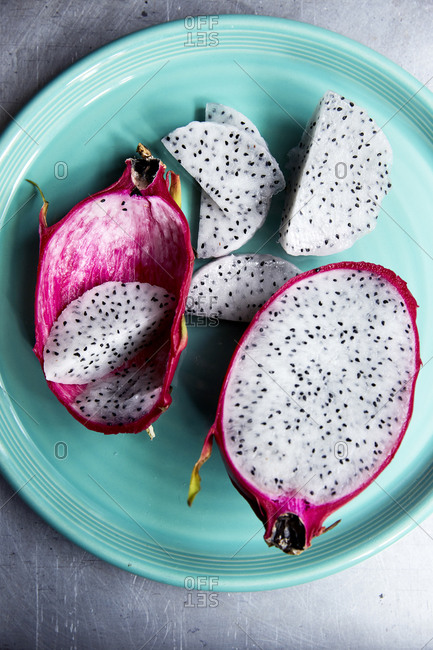 Dragon fruit cut open on a turquoise plate on a light background,