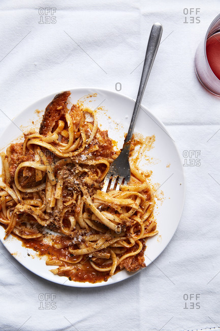 Fresh pasta in a tomato sauce with croutons served in a plate and a glass of wine on a white linen cloth,