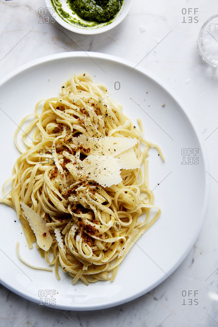 Fresh pasta topped with shavings of parmesan and toasted breadcrumbs on a marble countertop,