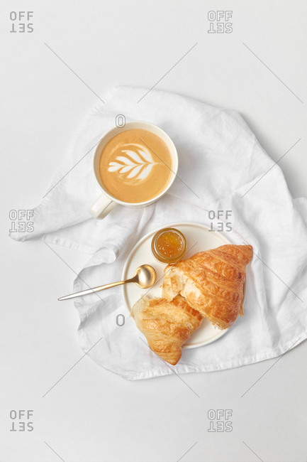 Homemade croissant with jam and cup of cappuccino on a white textile towel and light grey marble bakground, copy space. Top view. Continental breakfast concept.