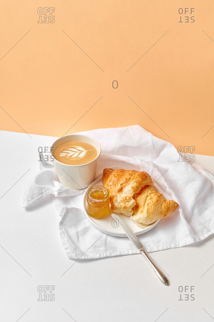 Freshly brewed cappuccino drink and ceramic plate with homemade croissant and jam on a textile white towel on a duotone background, copy space.