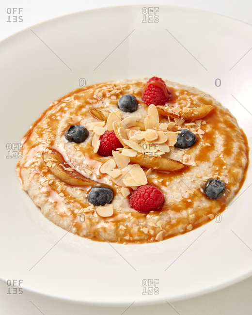 Healthy diet breakfast from freshly cooked porridge with natural organic berries and sweet honey in a ceramic plate, copy space.