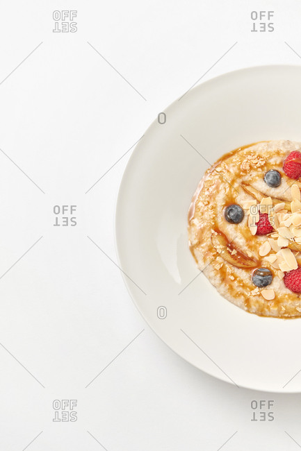 Half ceramic white plate of homemade freshly cooked porridge with natural organic berries and sweet honey in a ceramic plate, copy space.