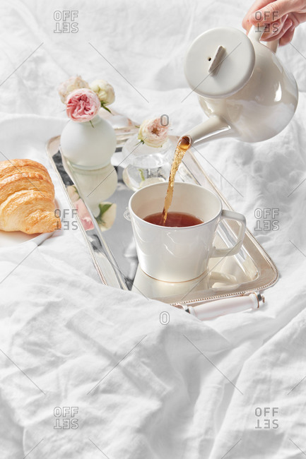 Process of pouring freshly brewed tea in a cup by female's hand for romantic breakfast with homemade croissant and vase with rose on a textile background, copy space.