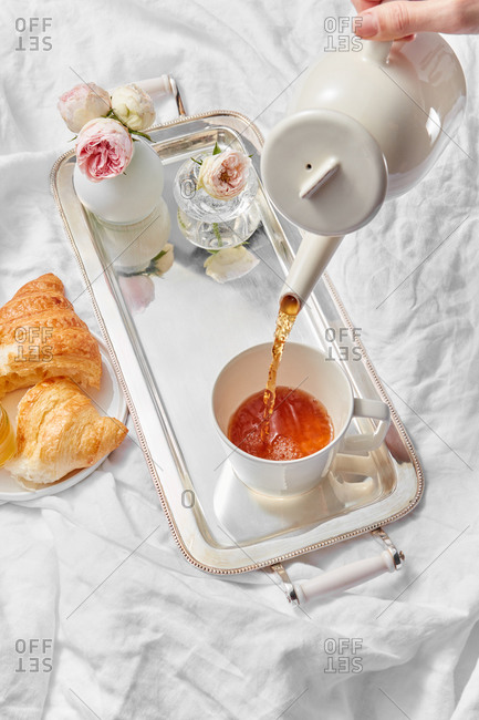 Process of pouring freshly brewed tea in a cup by woman's hand for romantic breakfast with sweet homemade croissant and vase with rose on a silver tray on a textile background, copy space.