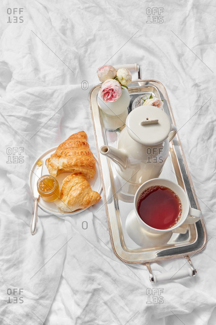 Morning romantic breakfast with tea pot and cup filled hot drink on a silver tray, freshly baked sweet homemade croissant with jam jar on a plate on a crumpled textile sheets, copy space.