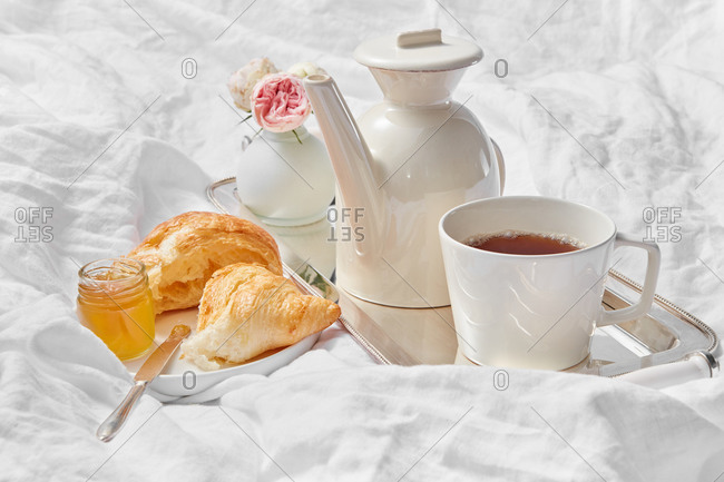 Morning romantic still life with porcelain tea pot and cup filled hot drink on a silver tray, freshly baked homemade sweet croissant with jam jar on a plate on a crumpled textile sheet, copy space.