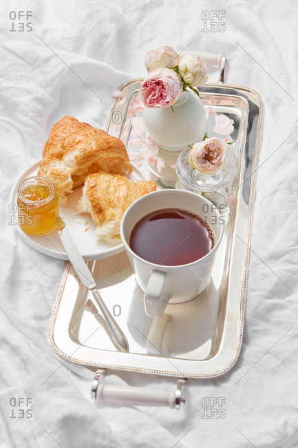 Delicious breakfast - silver tray with cup filled freshly brewed hot aromatic tea, flowers vase and croissant with sweet apricot jam on a plate on a crumpled textile background, copy space.