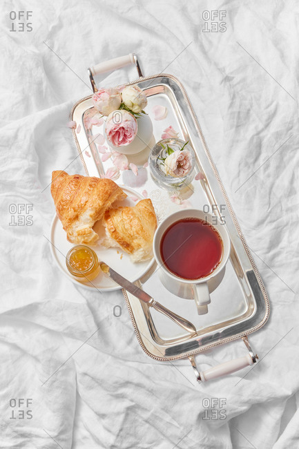 Top view of morning romantic breakfast with ceramic cup filled hot freshly brewed drink on a silver tray and homemade sweet croissant with jam jar on a crumpled textile background, copy space.