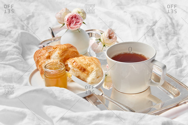 Beautiful romantic still life - silver tray with cup filled freshly brewed hot aromatic tea, flowers vase and croissant with sweet apricot jam on a plate on a crumpled textile background, copy space.