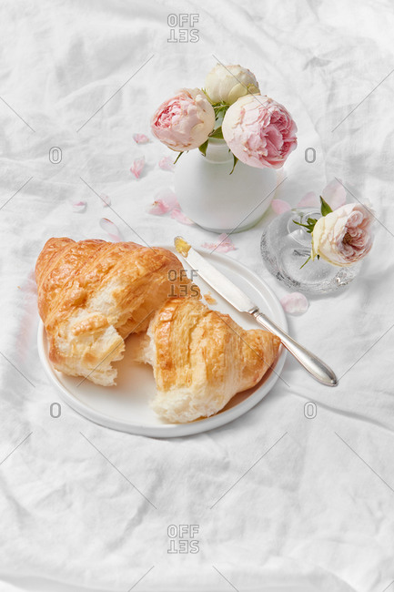 Freshly baked deliciouse homemade croissant on a plate and ceramic vase with fresh pink roses flowers on a textile crumpled background, copy space. Romantic morning breakfast.