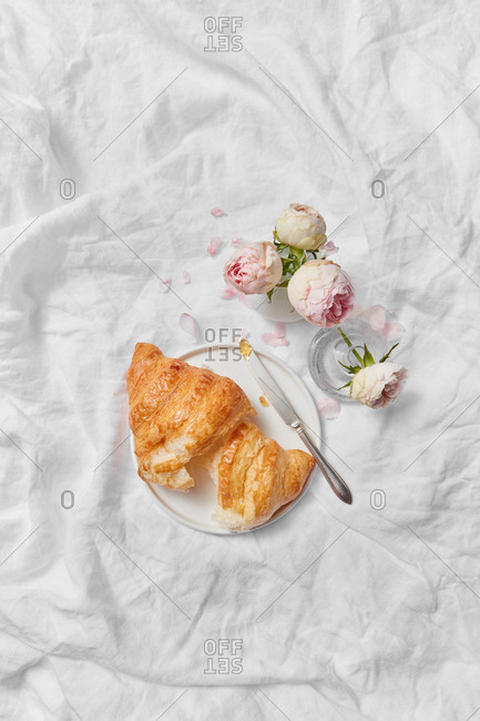 Top view of morning romantic composition with freshly baked homemade tasty sweet croissant on a plate and ceramic vase of aromatic roses flowers on a crumpled textile background, copy space.
