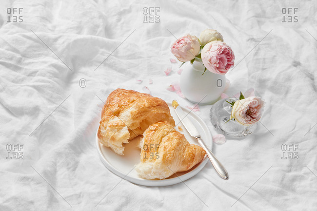 Morning wonderful still life from freshly baked homemade delicious sweet croissant and small ceramic vase of aromatic roses flowers on a crumpled textile background, copy space.