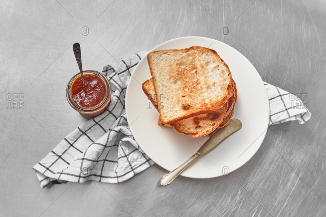 Healthy breakfast or snack with fresh grilled toasts and glass jar of sweet delicious jam on a light grey concrete background, served textile napkin, copy space.