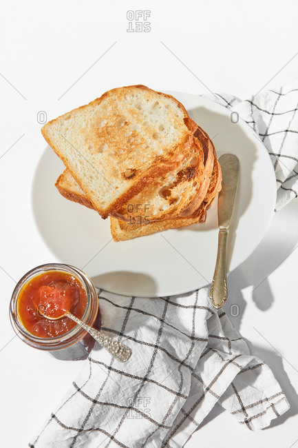 Healthy breakfast or snack with freshly baked toasts and glass jar of sweet apricot jam on a light grey concrete background, served textile napkin, copy space.
