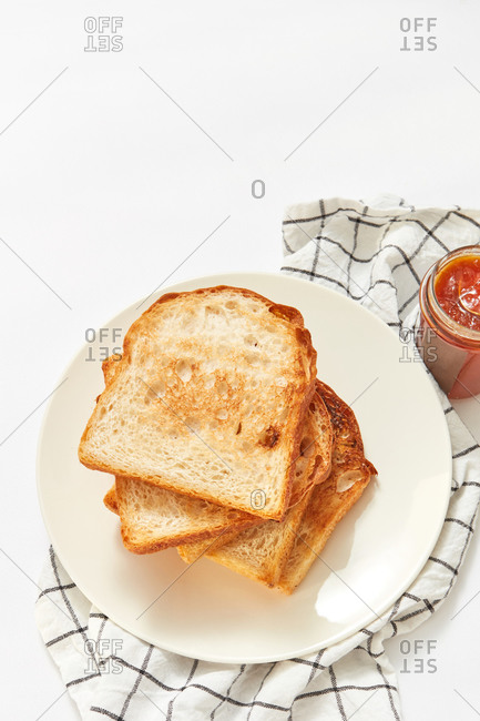 Healthy snack or breakfast with freshly baked toasts and glass jar of sweet apricot jam on a light grey concrete background, served textile napkin, copy space.
