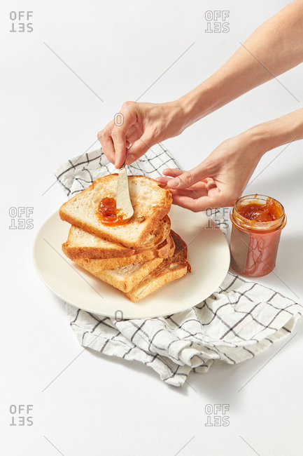 Process of preparing healthy breakfast by woman hand from freshly baked toasts and sweet apricot jam on a light grey concrete background, served textile napkin, copy space.