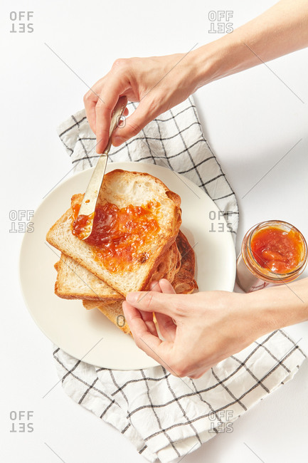 Process of cooking healthy snack or breakfast by female hands from freshly baked toasts and sweet fruits jam on a light grey concrete background, served textile napkin, copy space.