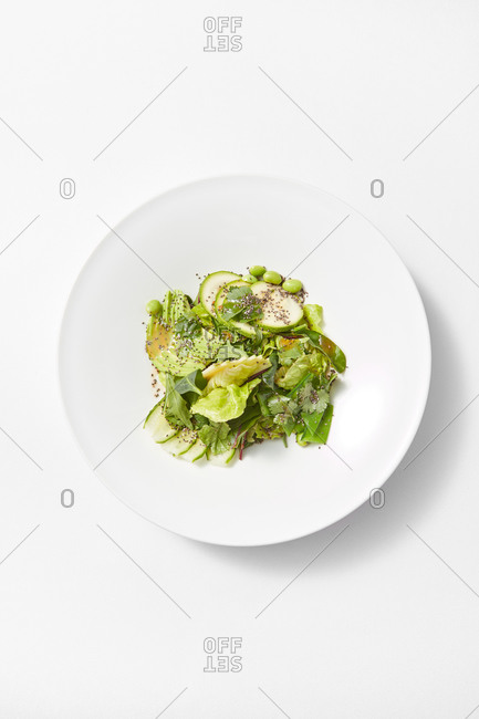 Top view ceramic plate with freshly cooked homemade vegan salad from sliced avocado, zucchini, green leaves and healthy seeds on a white background, copy space. Vegan concept.