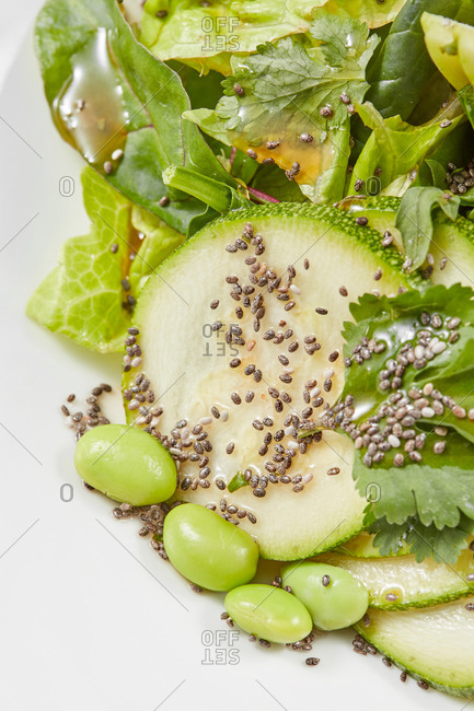 Healthy vegan homemade salad from raw organic ingredients sliced zucchini, green leaves, beans and natural seeds on a white background, copy space. Vegan concept.