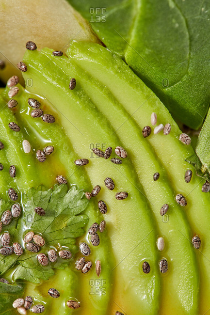 Natural vegetable vegan background. Macro view of freshly cooked homemade salad from organic natural ingredients - sliced avocado, greenery and seeds.