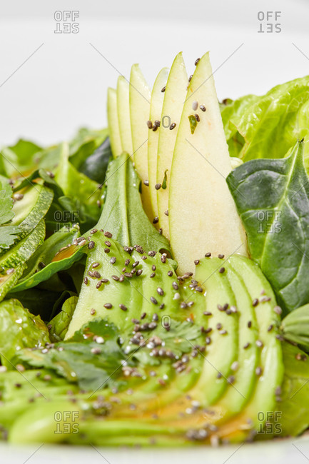 Homemade vegetarian salad from raw organic ingredients sliced avocado, green leaves, zucchini and natural seeds on a white background, copy space. Vegan concept. Close up view.