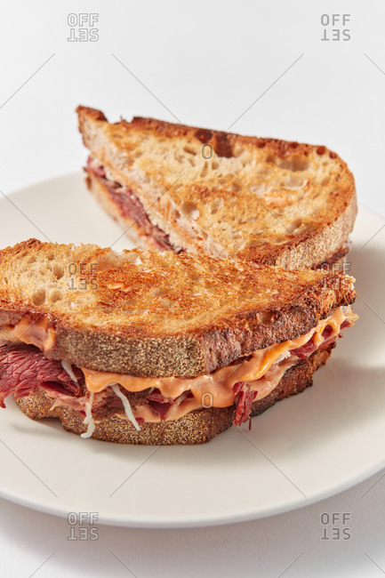 Close up view of freshly prepared homemade grilled sandwiches with ham and cheese on a ceramic plate on a white background, copy space.