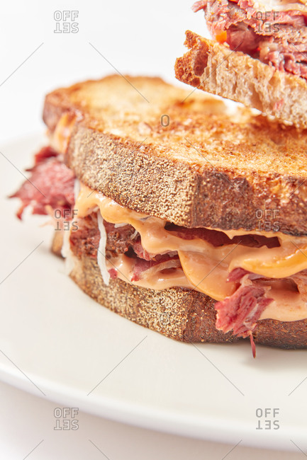 Close-up view of freshly prepared homemade hot grilled sandwiches on a ceramic plate and white background, copy space.