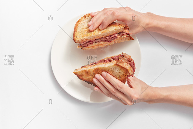 Two homemade freshly cooked healthy sandwiches with ham and cheese in a woman's hands above ceramic plate on a white background, copy space.